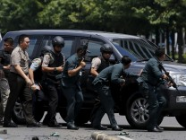 Indonesian police hold rifles while walking behind a car for protection in Jakarta