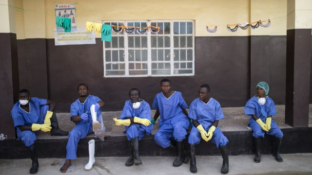 Health workers rest outside a quarantine zone at a Red Cross facility in the town of Koidu