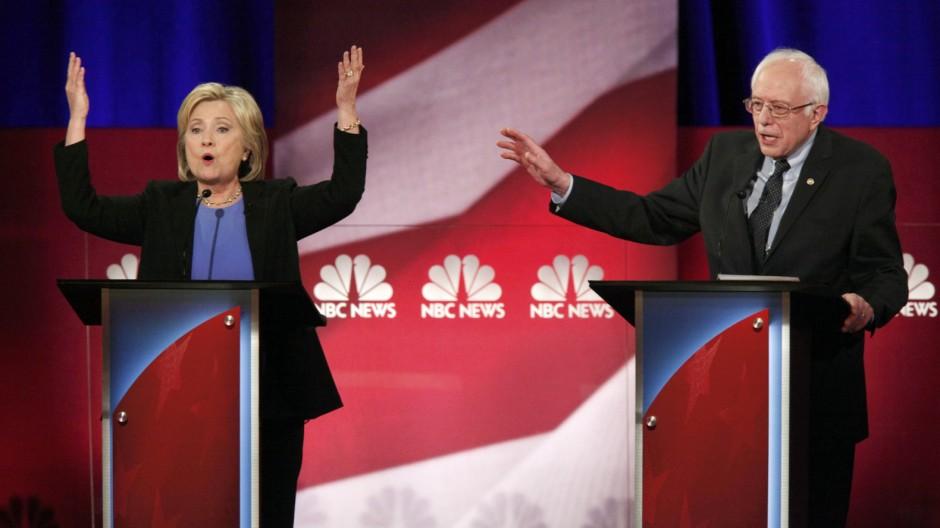 Democratic U.S. presidential candidate and former Secretary of State Hillary Clinton and rival candidate U.S. Senator Bernie Sanders speak simultaneously at the Democratic presidential candidates debate in Charleston