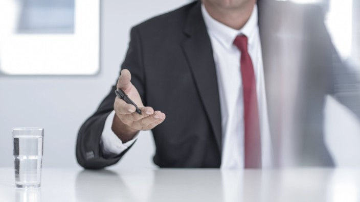 Businessman in office holding pen in hand mid section model released Symbolfoto property released P