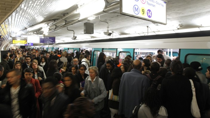 Commuters crowd into a train at Saint-Lazare metro station in Paris