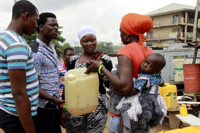 Woman with a baby on her back talks to others about her need for petrol to run her power generator, at the Area 10 shopping centre in Abuja, Nigeria