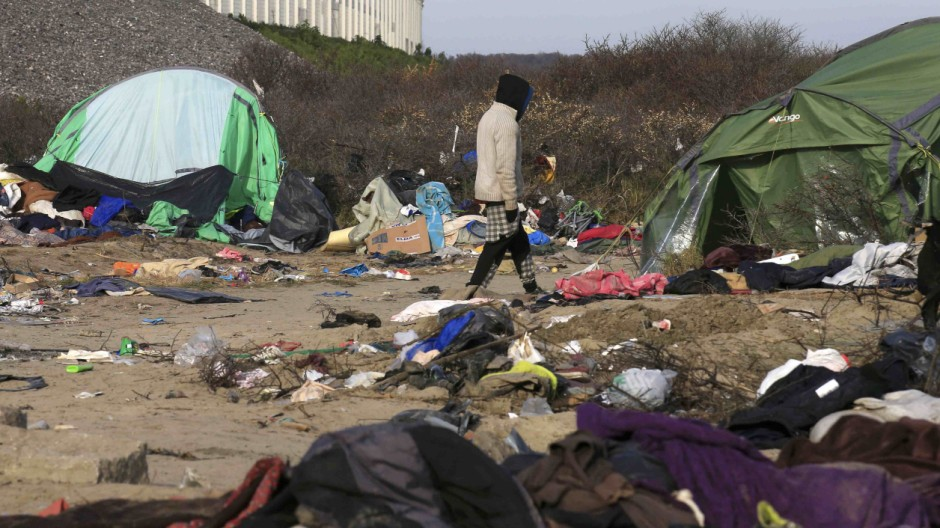 A migrant walks among dismantled shelters of the camp known as the 'Jungle' in Calais