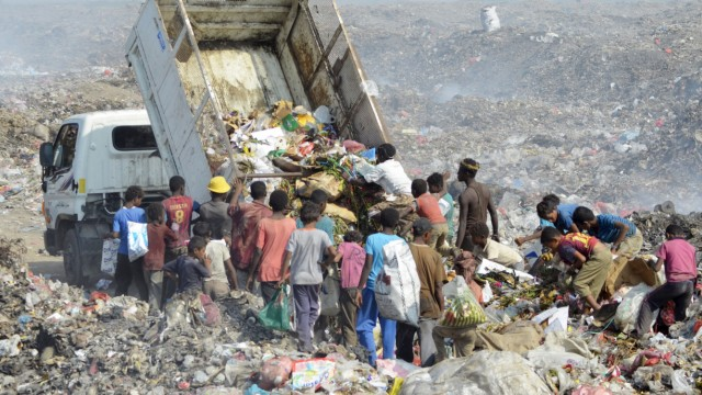 People collect recyclable waste at a rubbish dump outside Yemen's Red Sea port city of Houdieda