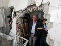 Resident Coordinator of the UN in Yemen, Jamie McGoldrick, inspects damage at a hospital in Taiz