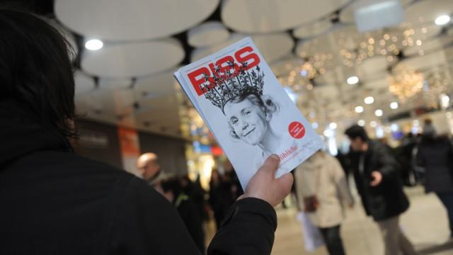 """Obdachloser verkauft Straßenzeitung """"Biss"""" in München, 2015"""