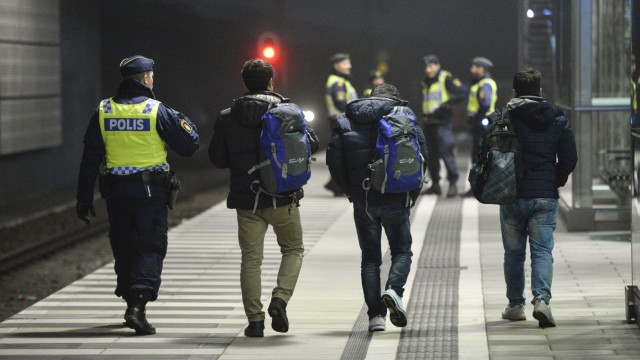 A police officer escorts migrants from a train at Hyllie station outside Malmo