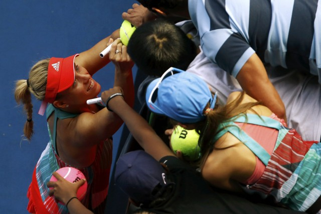 Germany's Kerber signs autographs after winning her semi-final match against Britain's Konta at the Australian Open tennis tournament at Melbourne Park