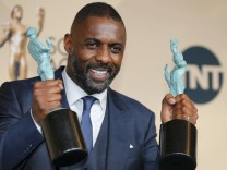 Idris Elba holds his awards as he poses backstage at the 22nd Screen Actors Guild Awards in Los Angeles