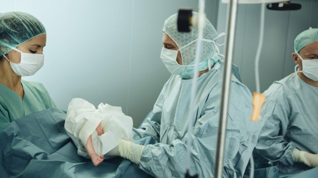 Surgeon handing over newborn to operating room nurse after c section PUBLICATIONxINxGERxSUIxAUTxHUNx