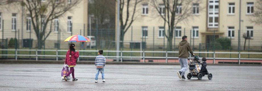 Migrant and his children walk in front of buildings in a refugee camp in Hameln
