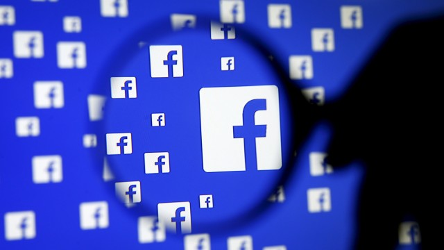 A man poses with a magnifier in front of a Facebook logo on display in this illustration taken in Sarajevoin this file photo