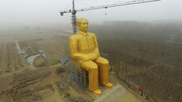 A crane is seen next to a giant statue of Chinese late chairman Mao Zedong under construction near crop fields in a village of Tongxu county, China