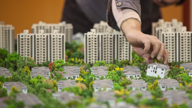 File photo of a worker installing models in preparation for a real estate exhibition in Shanghai