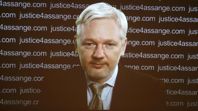 WikiLeaks founder Julian Assange appears on screen via video link during a news conference at the Frontline Club in London