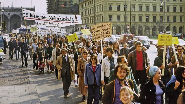 """Buch Karl Klühspies """"München nicht wie geplant""""; Protestmarsch auf der Ludwigstraße zur Rettung des Nikolaiplatzes und der Seidlvilla in Schwabing; ganz rechts, jeweils  mit geschultertem gelben Schild, ist Christian Ude mit seiner Frau zu sehen, 1976"""