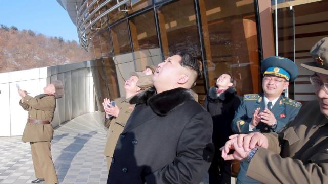 North Korean leader Kim Jong Un (C) watches a long range rocket launch into the air in North Korea