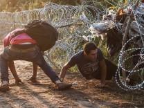 Flüchtlinge passieren Grenzzaun