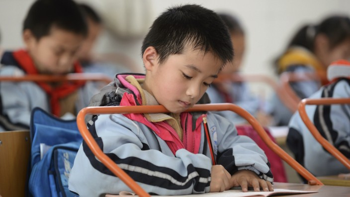 A pupil writes on a textbook as he sits on a refitted desk aiming to prevent student nearsightedness
