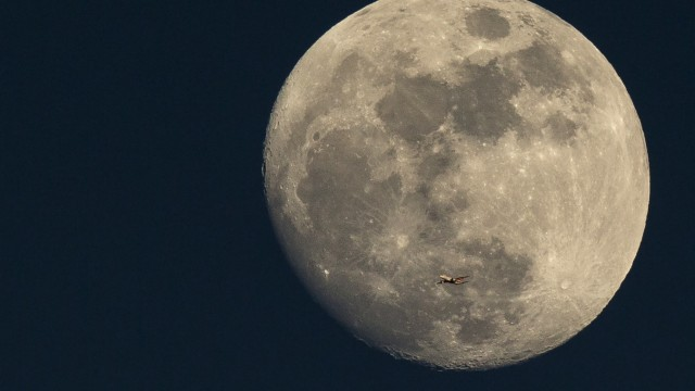 A Plane Is Dwarfed As It Flies Past The Moon