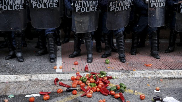 Vegetables are thrown in front of riot policemen guarding the Agriculture Ministry during a protest of Greek farmers against planned pension reforms in Athens