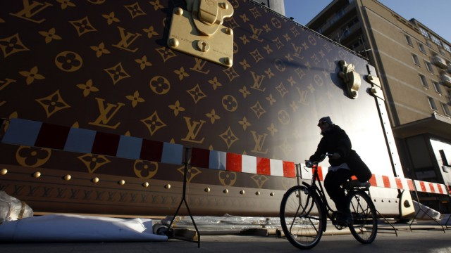 A woman rides her bicycle past a construction site where a giant advertisement wall presents a Louis Vuitton trunk at a shopping centre in Warsaw