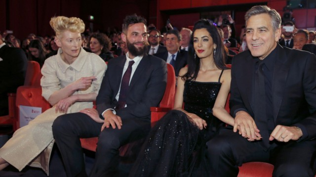 Actor Clooney his wife Amal actor Swinton and her partner Kopp take their seats for screening at opening gala of 66th Berlinale International Film Festival in Berlin