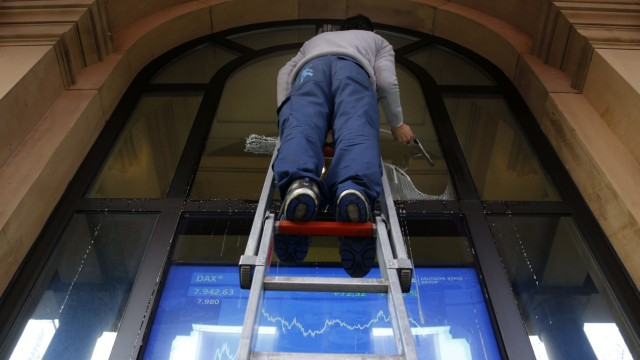A window cleaner cleans a window in front of a television screen showing the German share price index DAX outside the stock exchange in Frankfurt