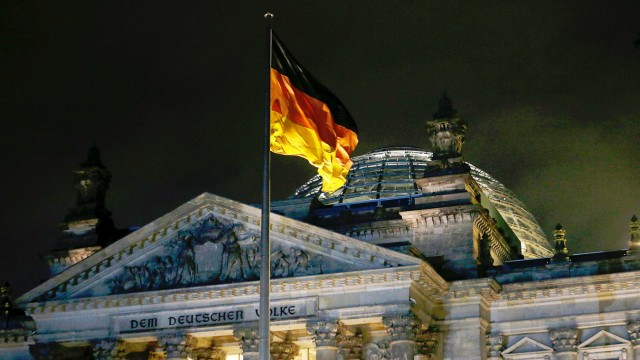 A German flag flutters in front of  Reichstag the seat of the German lower house of parliament Bundestag in Berlin