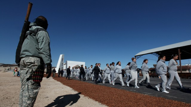 Policeman stands guard as female inmates return to their cells after a rehearsal of a song they will sing for Pope Francis in preparation for his upcoming visit to Cereso 3 prison in Ciudad Juarez