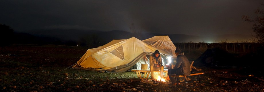 Migrants from Morocco, stranded at the Greek-Macedonian border, try to keep warm by an open fire next to their tent near the Greek village of Idomeni