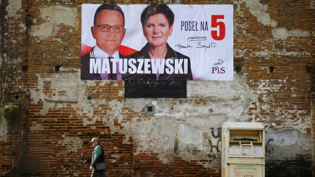 A man passes by an election poster depicting Law and Justice's candidate Matuszewski accompanied by the party's candidate for Prime Minister Szydlo in Leczyca