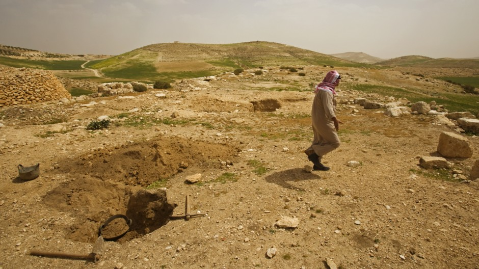 A looter walks away from an ancient site southeast of Hebron.