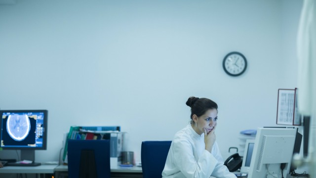 Young doctor in hospital looking at computer screen model released Symbolfoto property released PUBL
