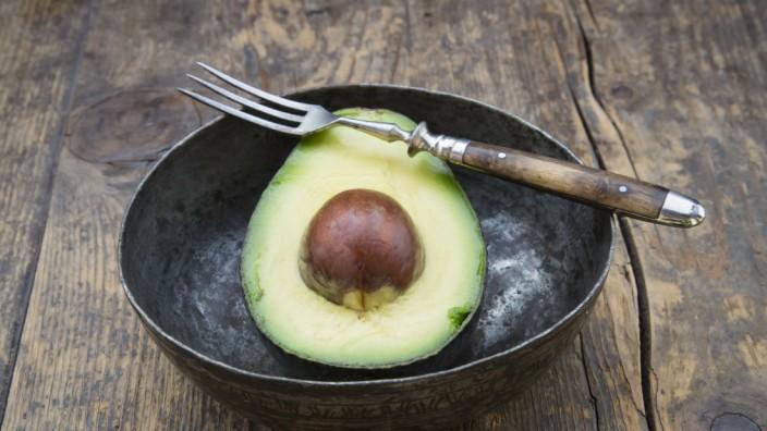 Bowl with half of avocado Persea Americana on wooden table PUBLICATIONxINxGERxSUIxAUTxHUNxONLY LVF