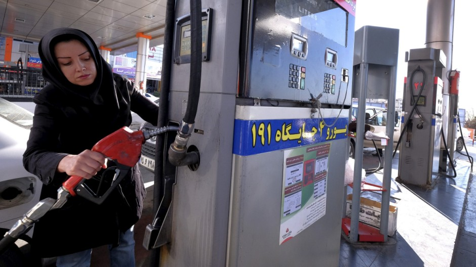 An Iranian woman puts a nozzle back after refuelling her car at a petrol station in Tehran