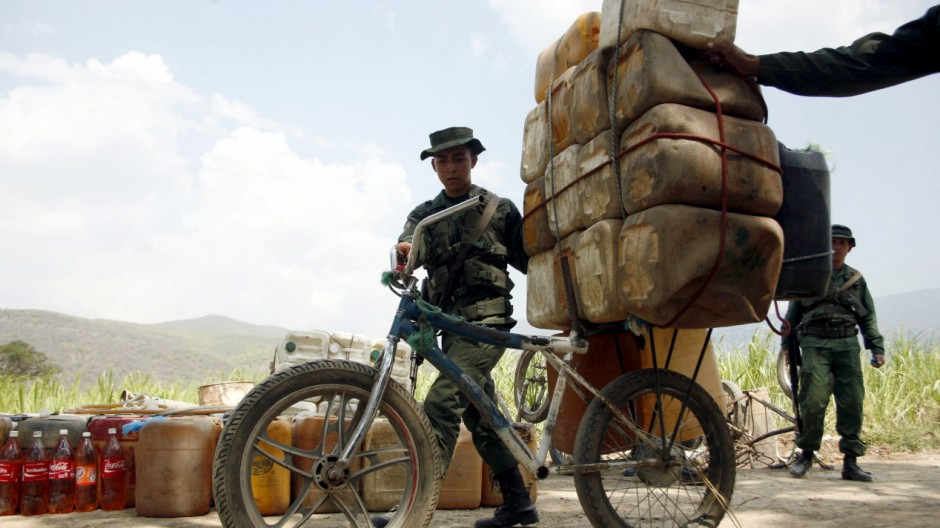 Venezuelan soldiers collect containers with gasoline abandoned by smugglers near the Colombian border in San Antonio