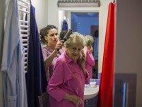 Gil Quiros of Spanish brushes resident's hair at SenVital elderly home in Kleinmachnow