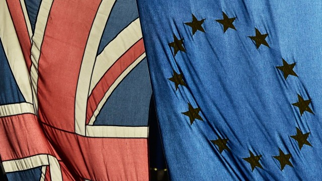 A British Union flag and a European Union flag hang from a building in central London