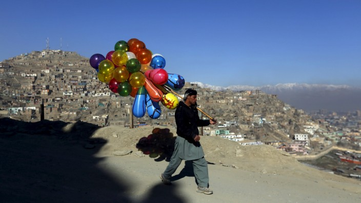 An Afghan man holds balloons for sale in Kabul, Afghanistan