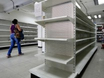 A woman walks past empty shelves at a drugstore in Caracas