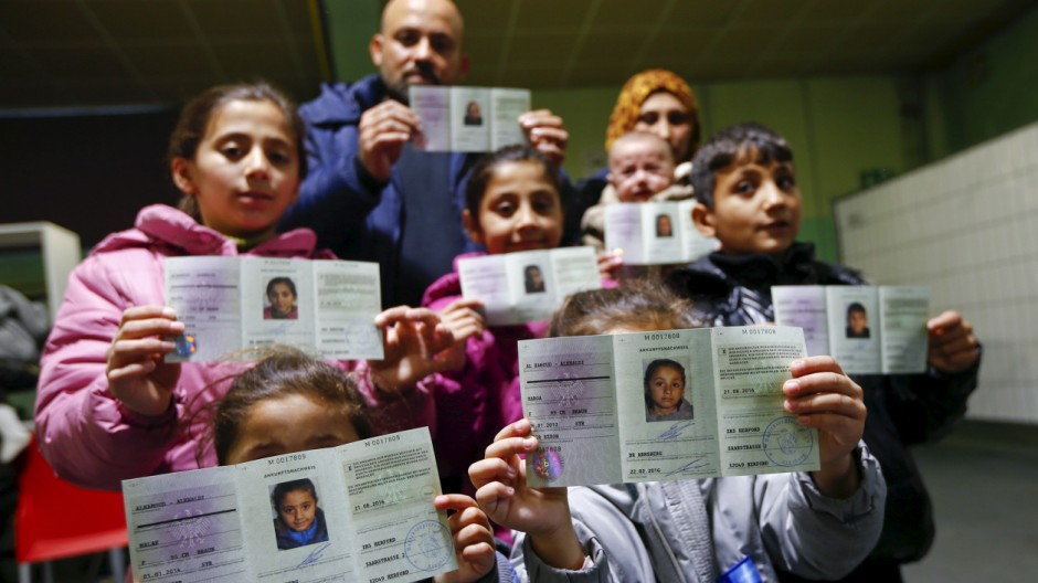 Syrian refugees present their newly issued initial German registration documents in Herford