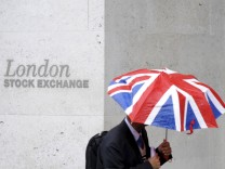 File photo of a worker sheltering from the rain as he passes the London Stock Exchange in the City of London