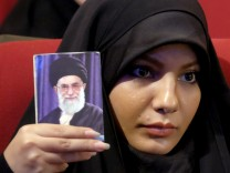 Woman holds a picture of Iran's Supreme Leader Ayatollah Ali Khamenei during a conservatives campaign gathering for the upcoming parliamentary elections and the upcoming vote on the Assembly of Experts, in Tehran