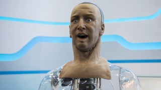 A humanoid robot named Han developed by Hanson Robotics reacts as the controller commands it via a mobile phone to make a facial expression during the Global Sources spring electronics show in Hong Kong