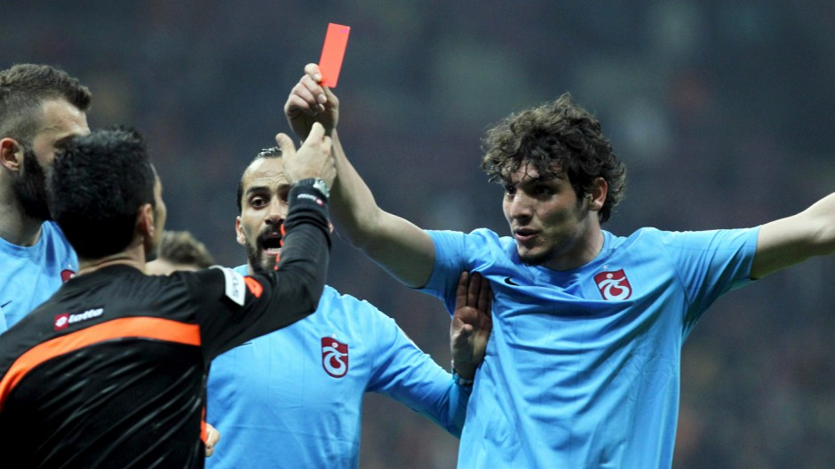 Trabzonspor's Salih Dursun shows a red card to referee Deniz Bitnel during the Turkish Super League soccer match between Galatasaray and Trabzonspor in Istanbul