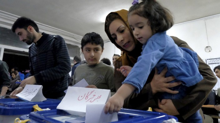 Iranian woman holding her daughter casts her ballot during elections for the parliament and Assembly of Experts, in Tehran