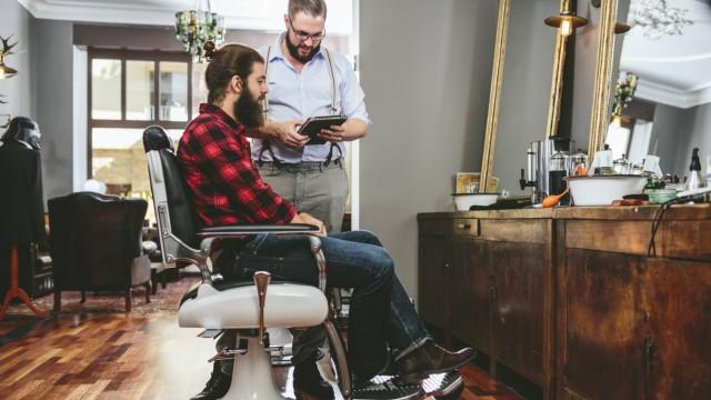Barber with customer using digital tablet model released Symbolfoto property released PUBLICATIONxIN