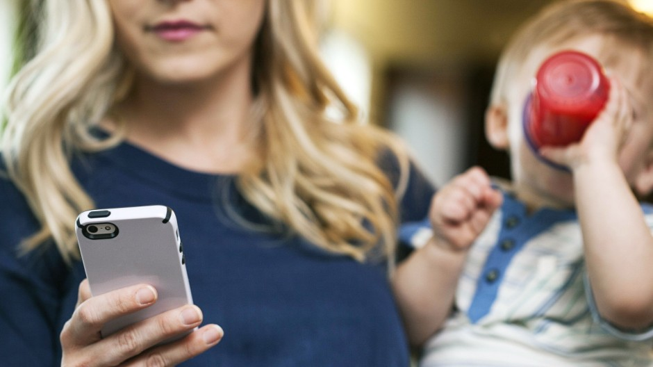 Mother checking SMS while holding child model released Symbolfoto PUBLICATIONxINxGERxSUIxAUTxHUNxONL