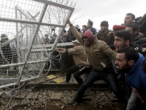 Stranded refugees and migrants try to bring down part of the border fence during a protest at the Greek-Macedonian border, near the Greek village of Idomeni